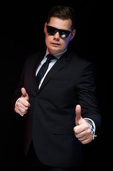 Pewny siebie przystojny elegancki biznesmen w okularach przeciwsłonecznych z kciukiem do góry pokazując swoją moc i zaufanie