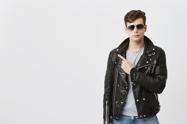 Pewny siebie przystojny facet w czarnej skórzanej kurtce z założonymi okularami przeciwsłonecznymi, wskazuje palcem wskazującym w przestrzeni kopii na reklamę lub tekst promocyjny. przystojny stylowy mężczyzna wskazuje na odległość
