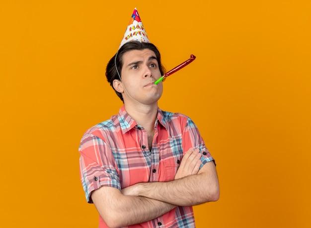 Pewny siebie przystojny kaukaski mężczyzna noszący czapkę urodzinową ze skrzyżowanymi rękami dmuchający gwizdek imprezowy patrząc w górę