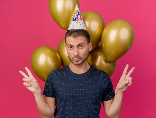 Pewny siebie przystojny kaukaski mężczyzna w czapce urodzinowej stoi przed balonami z helem, wskazując ręką znak zwycięstwa z dwiema rękami odizolowanymi na różowym tle z miejsca na kopię