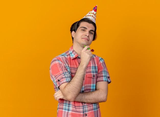 Pewny siebie przystojny kaukaski mężczyzna w czapce urodzinowej trzyma gwizdek na imprezę