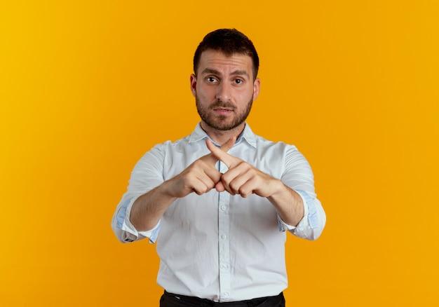 Pewny siebie przystojny mężczyzna krzyżuje palce gestykulacji żadnego znaku na białym tle na pomarańczowej ścianie