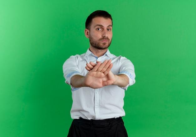 Pewny siebie przystojny mężczyzna krzyżuje ręce, gestykulując nie na białym tle na zielonej ścianie