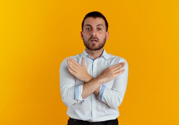 Pewny siebie przystojny mężczyzna krzyżuje ręce gestykulując żadnego znaku na białym tle na pomarańczowej ścianie