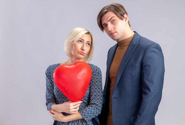 Pewny siebie przystojny mężczyzna stojący z ładną blond kobietą trzymającą balon w kształcie czerwonego serca na walentynki
