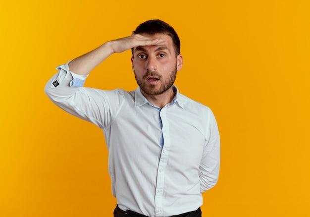 Pewny siebie przystojny mężczyzna trzyma dłoń na czole, próbując zobaczyć na białym tle na pomarańczowej ścianie