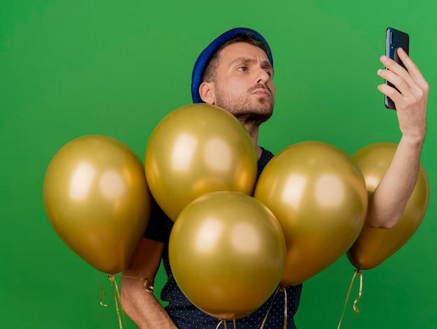 Pewny siebie przystojny mężczyzna ubrany w niebieski kapelusz strony stoi z balonami helowymi, trzymając i patrząc na na białym tle na zielonej ścianie z miejsca na kopię