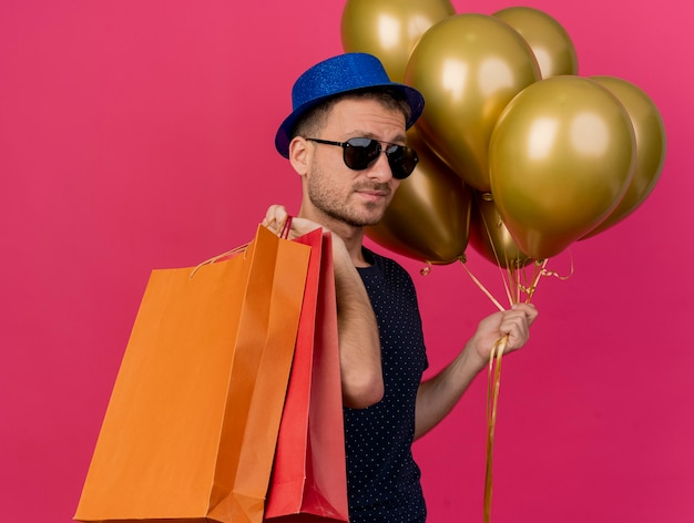 Pewny siebie przystojny mężczyzna w okularach przeciwsłonecznych w niebieskim kapeluszu stoi bokiem, trzymając balony z helem i papierowe torby na zakupy na różowej ścianie