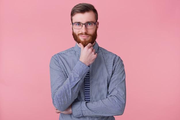 Pewny siebie, przystojny młody brodacz w okularach, trzyma rękę na brodzie, myśli o czymś, buduje plan, rozważa fajny pomysł. pojedynczo na tle oink.