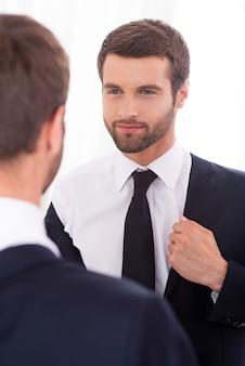 Pewny siebie. przystojny młody mężczyzna ubrany w kurtkę i uśmiechający się stojąc przed lustrem