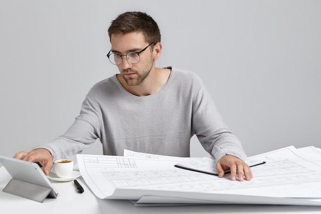 Pewny siebie robotnik uważnie zagląda do komputera typu tablet, pracuje nad projektem budowlanym