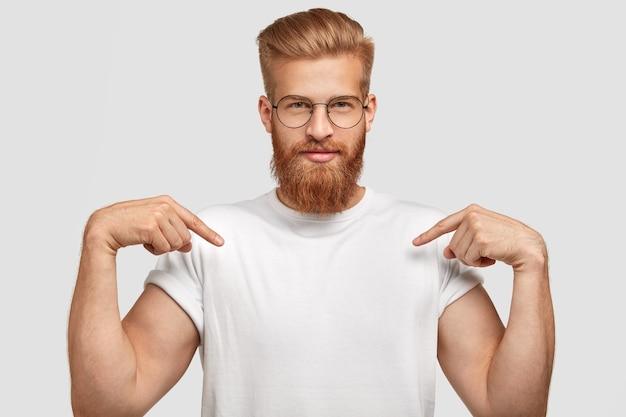 Pewny siebie rudy mężczyzna z modną fryzurą, ubrany w casualową koszulkę, wskazuje dwoma przednimi palcami