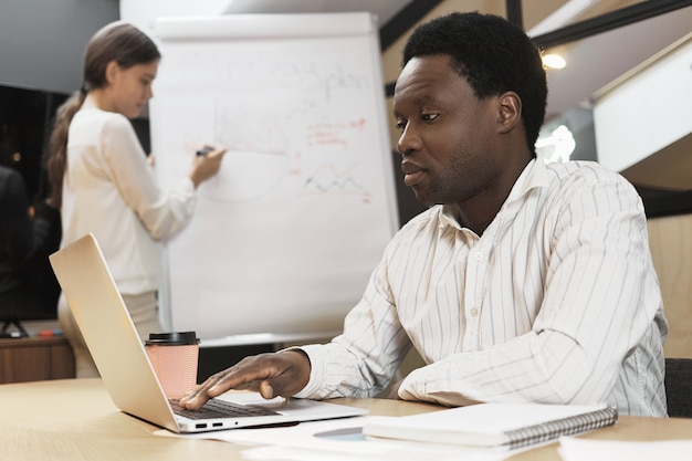 Pewny siebie, skoncentrowany afrykański mężczyzna za pomocą przenośnego gadżetu elektronicznego przy biurku