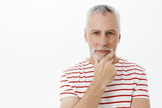 Pewny siebie starszy brodaty mężczyzna myśli, patrząc zamyślony