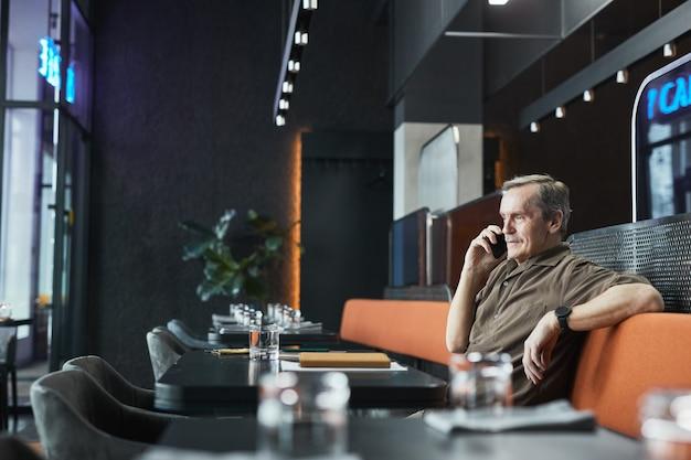 Pewny siebie starszy menedżer rasy kaukaskiej w brązowej koszuli siedzi w zrelaksowanej pozie na siedzeniu kawiarni bistro i rozmawia przez telefon