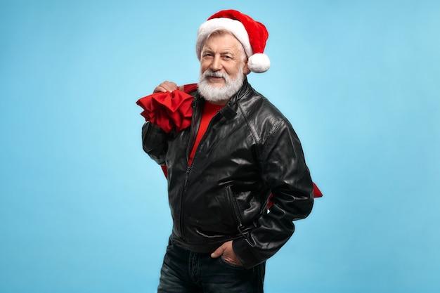 Pewny siebie starszy mężczyzna w świątecznym kapeluszu z torbą świętego mikołaja w studio