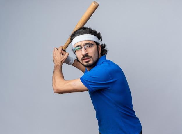 Pewny siebie stojąc w pozie do walki młody sportowy mężczyzna noszący opaskę z opaską na nadgarstek trzymający kij bejsbolowy