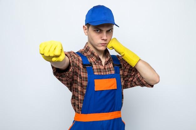 Pewny siebie stojąc w pozie do walki młody sprzątacz ubrany w mundur i czapkę z rękawiczkami