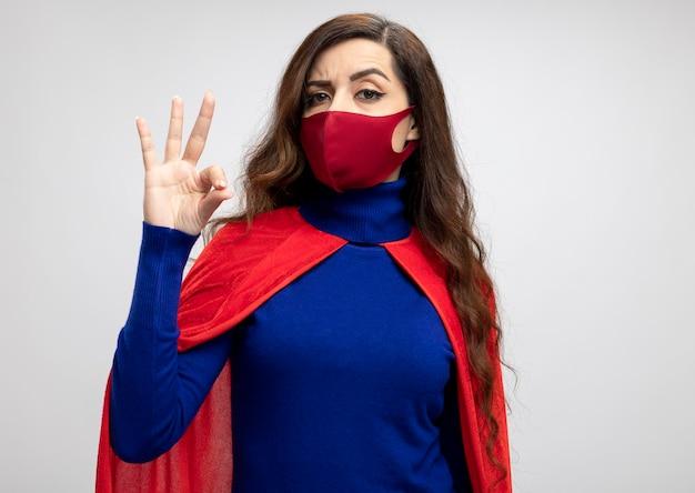 Pewny siebie superbohater kaukaski dziewczyna z czerwoną peleryną na sobie czerwoną maskę ochronną