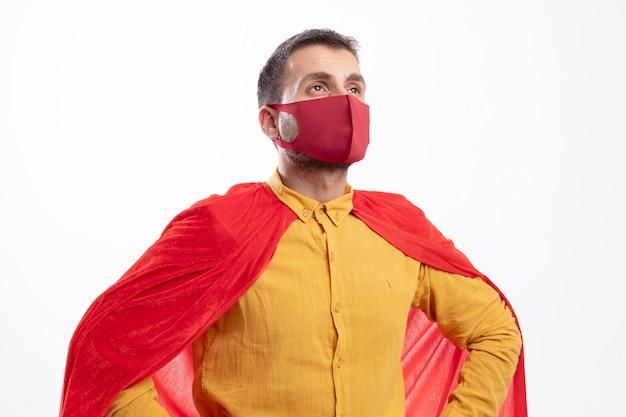 Pewny siebie superbohater mężczyzna z czerwonym płaszczem w czerwonej masce kładzie ręce na talii i patrzy z boku na białym tle na białej ścianie