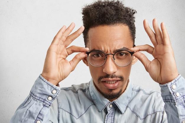 Pewny siebie surowo poważny mężczyzna dokładnie patrzy przez okrągłe okulary, próbuje coś zobaczyć