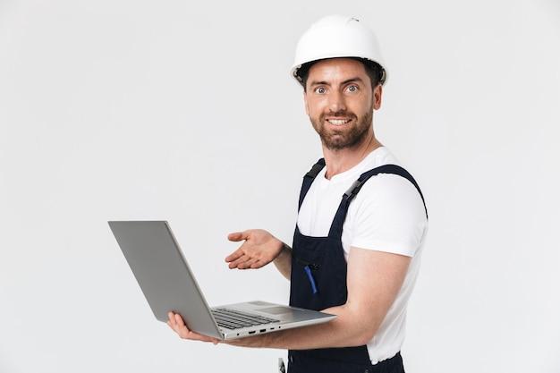 Pewny siebie, szczęśliwy brodaty budowniczy mężczyzna ubrany w kombinezon i kask stojący na białym tle nad białą ścianą, używający laptopa