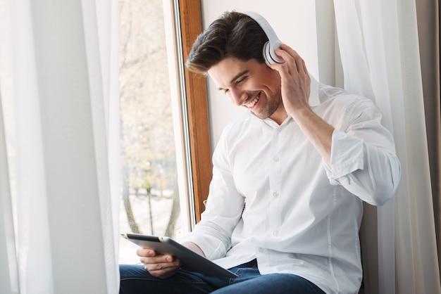 Pewny siebie szczęśliwy człowiek ubrany w białą koszulę za pomocą komputera typu tablet i słuchawek, siedząc przy oknie w salonie