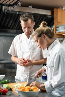 Pewny siebie szef kuchni w mundurze patrzący na swoją młodą praktykantkę krojącą świeżą cukinię, stojąc przy stole w kuchni restauracji