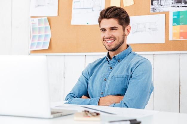 Pewny siebie uśmiechnięty szczęśliwy biznesmen siedzący przy stole z założonymi rękoma w biurze