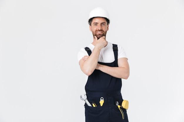 Pewny siebie zamyślony brodaty budowniczy mężczyzna ubrany w kombinezon i kask stojący na białym tle nad białą ścianą