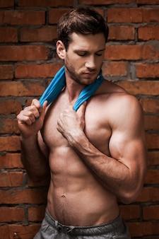 Pewny swojego idealnego ciała. przystojny młody muskularny mężczyzna owinięty w podkoszulek!