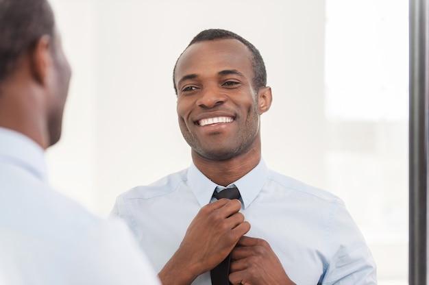 Pewny swojego wyglądu. młody afrykanin dopasowujący krawat stojąc przed lustrem