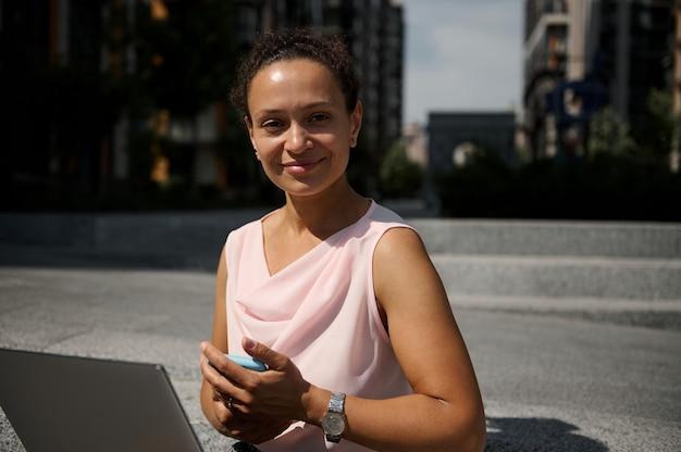 Pewny szczegół portret atrakcyjnej kobiety biznesu rasy mieszanej z laptopem i smartfonem, patrząc na kamerę siedzącą na schodach na tle miejskich wysokich budynków