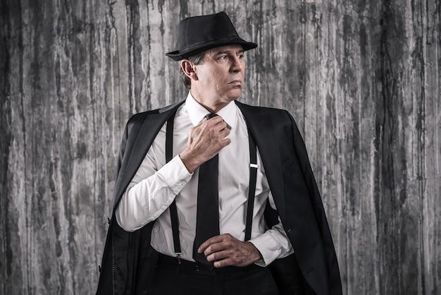 Pewny szef mafii. apodyktyczny starszy mężczyzna w gangsterskim ubraniu, poprawiający krawat i odwracający wzrok, stojąc pod ścianą