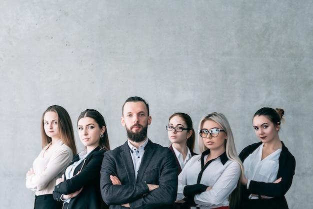 Pewny trener biznesu. coaching korporacyjny. zespół profesjonalistów firmy pozujących ze skrzyżowanymi rękami
