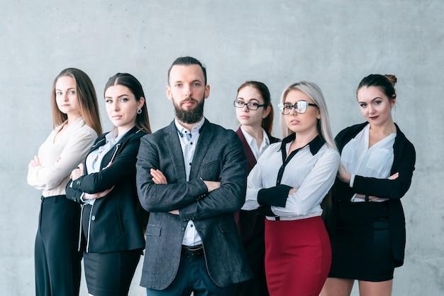 Pewny trener biznesu. zaawansowane szkolenie korporacyjne. zespół profesjonalistów firmy pozujących z założonymi rękami.
