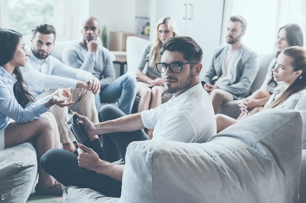 Pewny trener życia. grupa młodych ludzi siedzących w kręgu i dyskutujących o czymś, podczas gdy młody mężczyzna trzyma cyfrowy tablet i patrzy przez ramię
