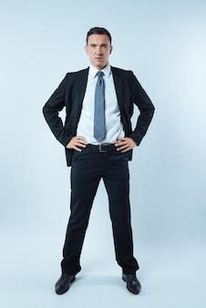 Pewny wygląd. inteligentny ładny przystojny mężczyzna stojący na niebieskim tle i dający pewność siebie, będąc profesjonalnym biznesmenem