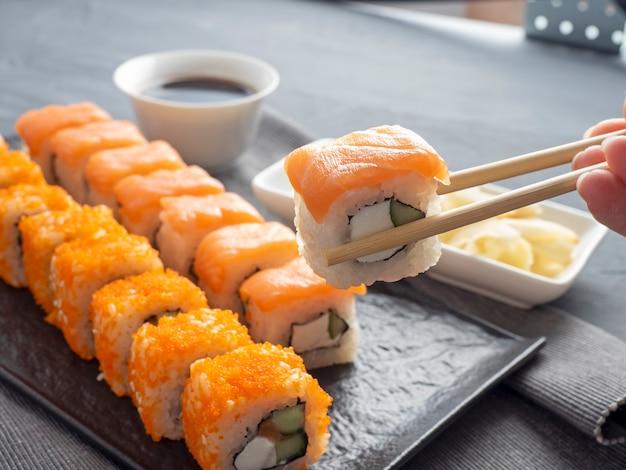 Philadelphia i california toczy się na teksturowanej ciemnej płycie. jedna rolka jest trzymana w kijach babci nad innymi. obok sosu sojowego, wasabi i imbiru. widok z boku. kuchnia japońska