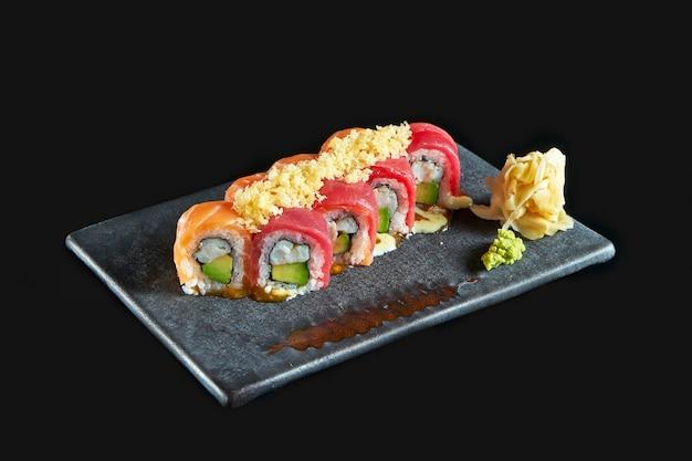 Philadelphia roll sushi z łososiem i krabem z tuńczyka, awokado, podany na ciemnym talerzu z wasabi i imbirem. izolacja na czarnym tle. japońskie jedzenie