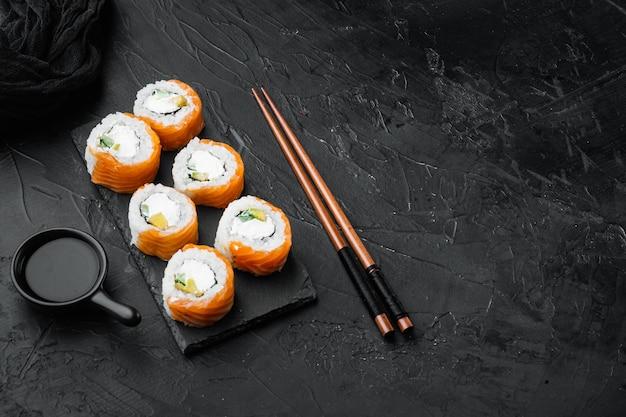 Philadelphia roll sushi z łososiem, krewetką, awokado, serkiem śmietankowym, na czarnym kamieniu
