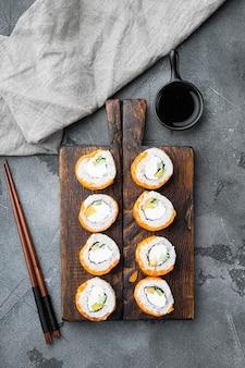 Philadelphia roll sushi z łososiem, krewetkami, awokado, serkiem śmietankowym, na szarym kamiennym tle, widok z góry płasko leżący