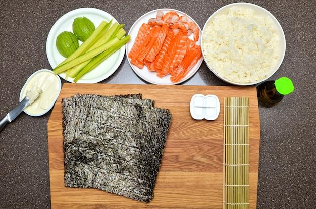 Philadelphia sushi maki i składniki, na drewnianej desce do krojenia, widok z góry, kopia przestrzeń na arkuszu nori.