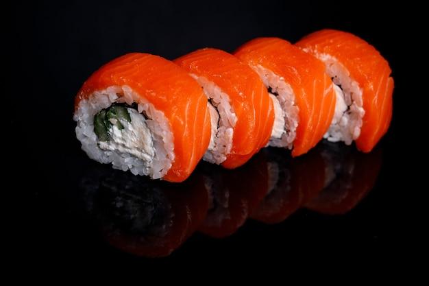 Philadelphia sushi roll na czarnym tle z refleksji.