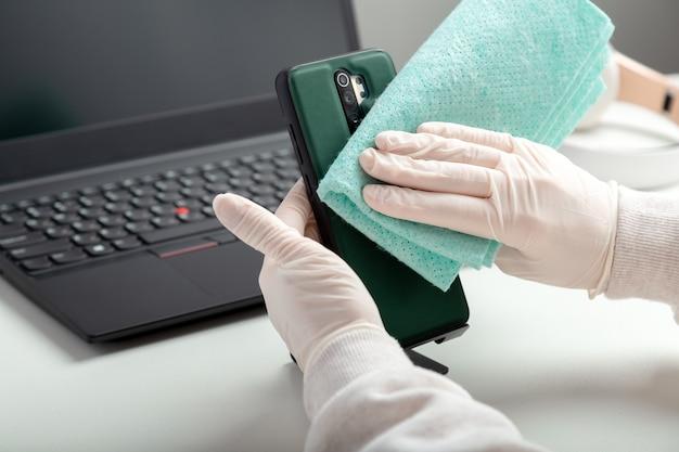 Phome zdezynfekować alkoholowym środkiem dezynfekującym. kobieta w rękawiczkach medycznych podczas covid wyciera chusteczki i środek dezynfekujący. 19. ochrona higieny zapobieganie infekcji koronawirusem, zarazkami, bakteriami