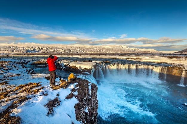 Photoghaper robi zdjęcie przy wodospadzie godafoss zimą, islandia.