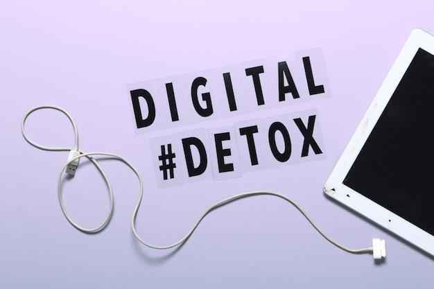 Phrase digital detox i pęknięty tablet. fioletowe tło, hashtag, widok z góry.