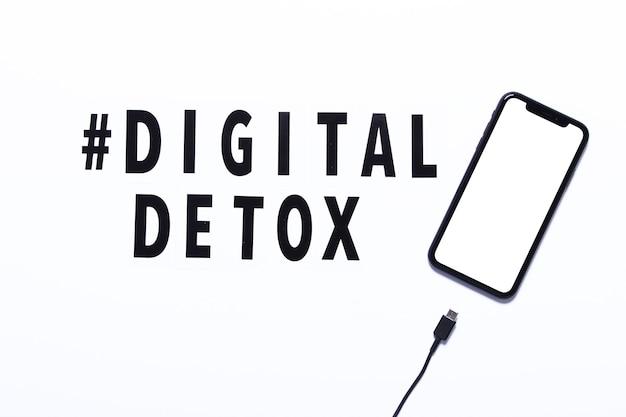 Phrase digital detox i smartfon z odłączanym kablem ładującym. białe tło, hashtag, widok z góry.