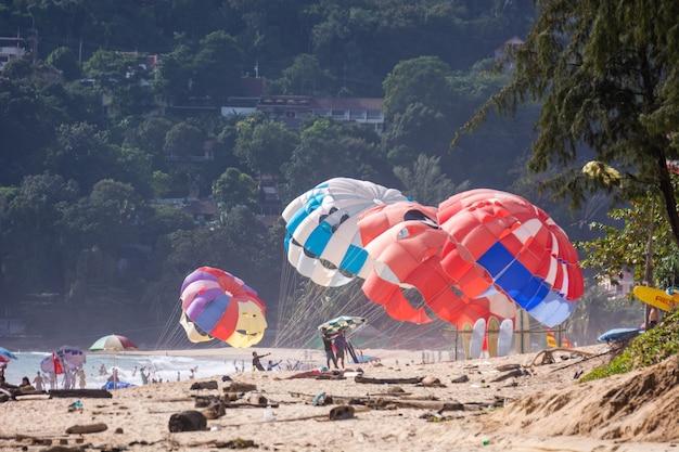 Phuket tajlandia, czerwiec, - 23, 2018: podróżnicy bawić się kolorowego parasailing przy ka ron plażą.