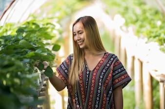 Piękna średniorolna kobieta sprawdza truskawki gospodarstwo rolne